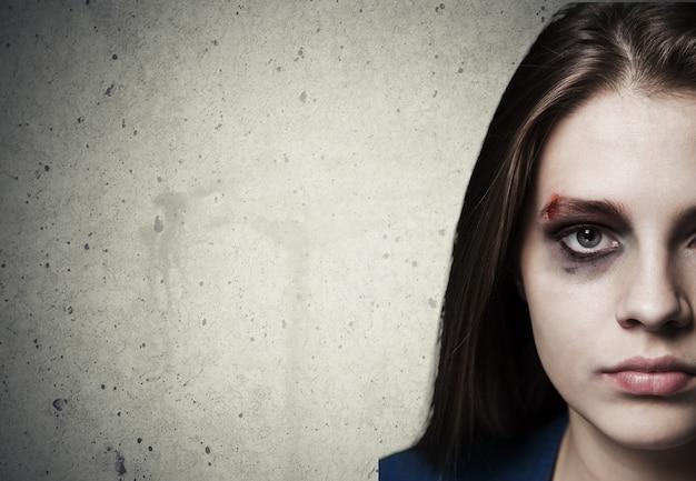 Грустная избитая девушка с ранами на лице смотрит в камеру с глубоким взглядом