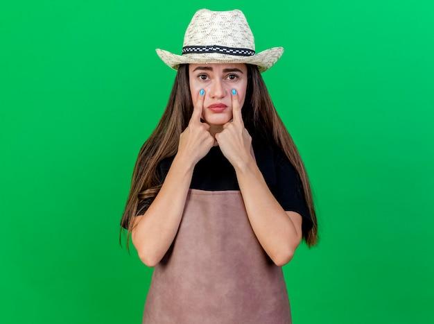 Sad beautiful gardener girl in uniform wearing gardening hat putting fingers at eyes isolated on green