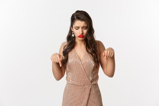 Грустная красивая девушка указывая пальцами вниз и дуется, в платье для рождественской вечеринки, разочарованно смотрит, стоя на белом фоне.