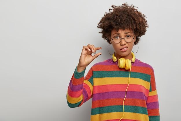 悲しい美しい女性は小さなことを示し、小さなジェスチャーをし、不快に顔をしかめ、カジュアルな服を着て、大きな丸い眼鏡をかけます