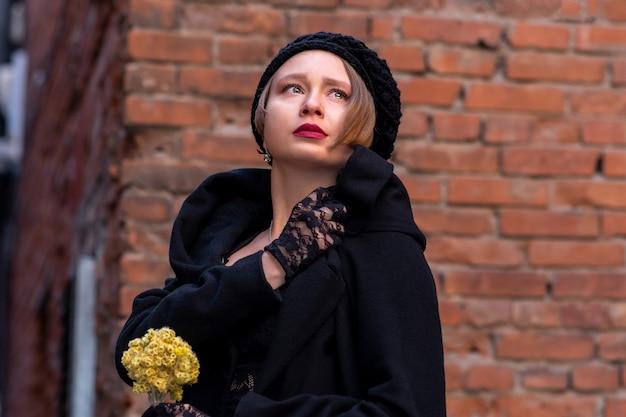 벽돌 벽 배경에 복고 스타일의 슬픈 아름다운 여자
