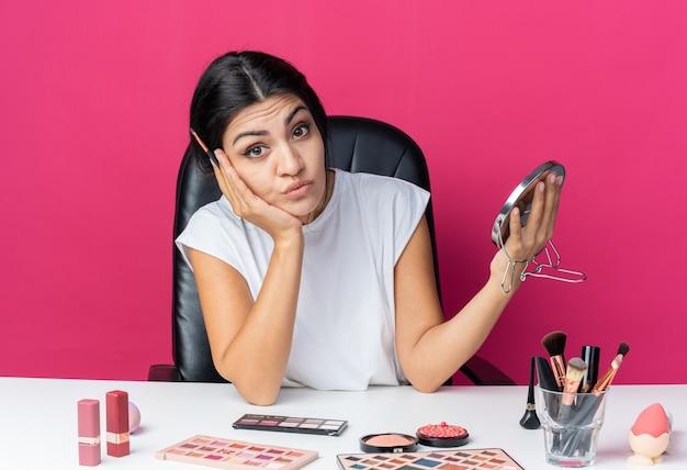 La bella donna triste si siede al tavolo con gli strumenti per il trucco che tengono il pennello per il trucco con lo specchio che mette la mano sulla guancia