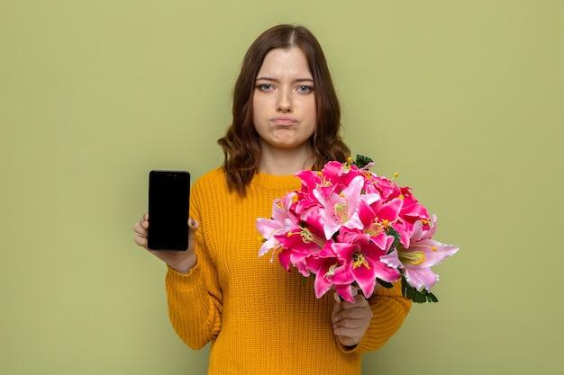 행복 한 여성의 날에 슬픈 아름 다운 소녀 올리브 녹색 벽에 전화와 꽃다발을 들고