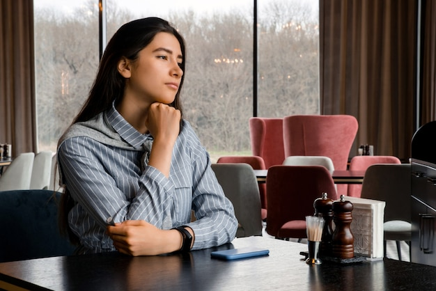 Sad beautiful young woman with smartphone waiting for boyfriend in restaurant