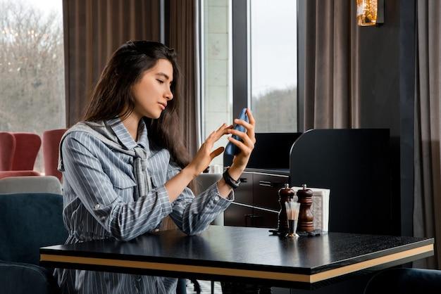 レストランで彼氏を待っているスマートフォンと悲しい美しい若い女性