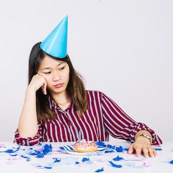 Triste ragazza di compleanno con ciambella