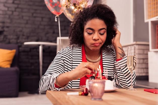 Печальный день рождения. грустная несчастная женщина зажигает свечи на торте во время дня рождения