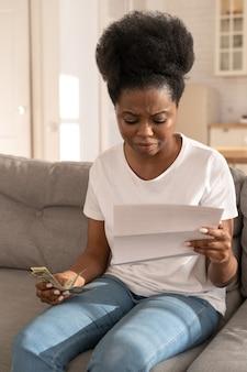 Грустная черная девушка держит последние наличные деньги, чувствуя беспокойство по поводу долга или банкротства, сидя дома.