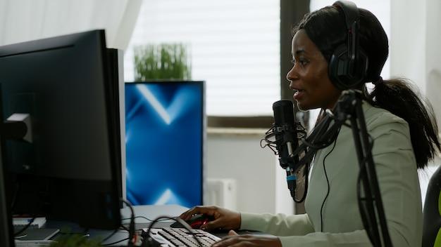 競争に負けているゲームのホームスタジオでヘッドフォンストリーミングビデオゲームを持つ悲しい黒人女性ゲーマー。強力なコンピューターでゲームをプレイするためにオンラインで他のプレイヤーと話しているプロのプレイヤー