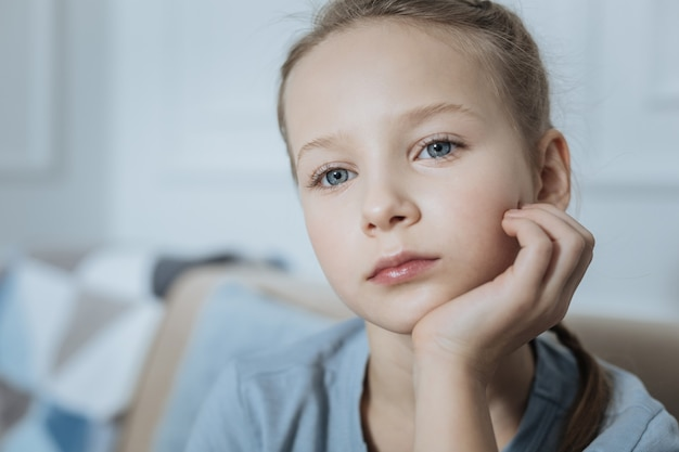 Sad blond blue-eyed little girl thinking and holding her head with her hand while looking in the distance