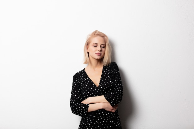 Sad blonde girl in a black dress on a white background