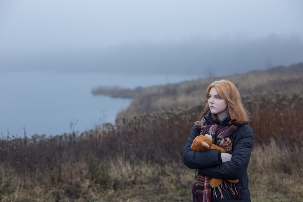 Sad blonde teenager woman hugging teddy bear by foggy lake. concept of adolescence and adolescent problems.