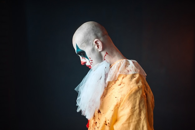 Sad bloody clown with makeup in carnival costume, side view