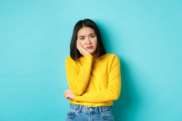 Sad and bored asian girl looking reluctant and unamused at camera, leaning face on hand, standing over blue background.
