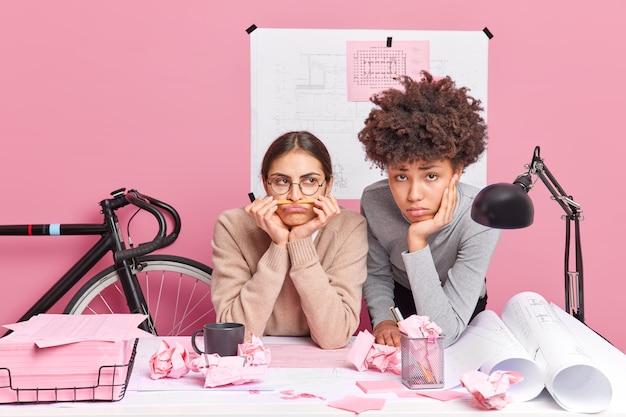 Грустно скучающие разноплановые женщины, недовольные рабочим процессом, пытаются найти решение проблемы, готовятся к стартап-встрече, позируют в коворкинге, работают над планировкой нового здания. концепция мозгового штурма