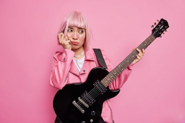 悲しい退屈な女性のロッカーは、エレクトリックアコースティックギターを保持し、彼女の新しいアルバムの新しい曲を作成し、ジャケットに身を包んだピンクの髪型をしています