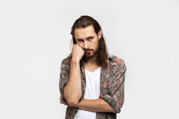 Sad bored man, depression and sadness, without interest in what is happening. hipster traveler stylish carefree man on a white studio background, people lifestyle