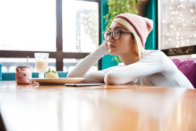 Sad bored young woman sitting at the table in cafe