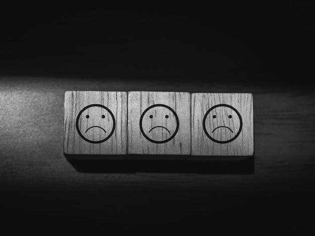 暗い背景、黒と白のスタイルの木製の立方体ブロックの悲しい、退屈な顔の絵文字。満足していない、フィードバックレビュー、満足サービスのコンセプト。