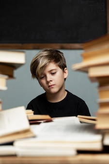 A sad boy in a black t-shirt sits at a table with a bunch of books