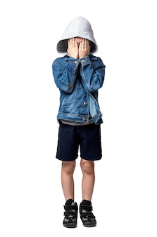 Sad boy in a denim jacket, covers his face  on a white isolated background