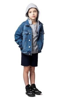 Sad boy in denim jacket, holds hands in pockets  on white isolated background