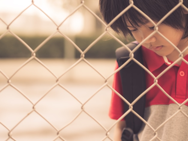 Sad boy behind fence mesh netting. emotions concept.