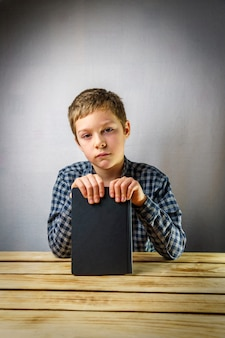 Sad boy from 7 to 9 years old, holding a book in his hands, on a gray background at a wooden table.