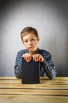 Грустный мальчик от 7 до 9 лет, держа книгу в руках, на сером фоне за деревянным столом.