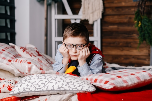 A sad boy in glasses lies on a bed