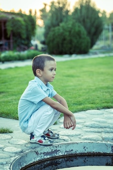 A sad boy is sitting on the street alone, unhappy lonely child, blue tone