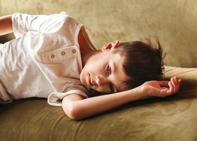 A sad boy lies on the sofa in the children's bedroom. children's emotions.