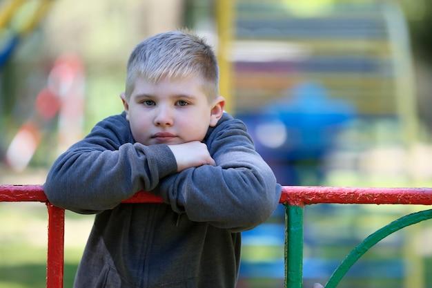 Грустный мальчик на спортивном турнике. несчастный дошкольник