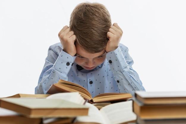 Грустный мальчик сидит за столом с множеством книг. ребенок 9-10 лет в синей рубашке обхватил голову руками. белый фон.