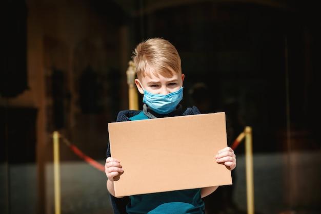 의료 얼굴 마스크를 쓰고 슬픈 소년