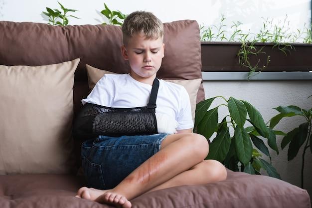 腕を骨折し、子供の手の石膏に傷を負った悲しい少年