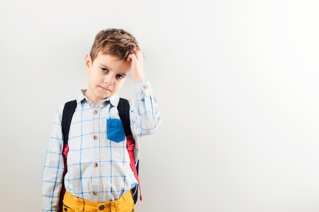 A sad boy with a backpack against a white background.