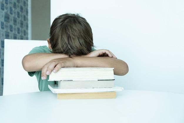 책을 가진 슬픈 소년은 학교 숙제를 합니다. 학교로 돌아가다. 교과서와 함께 불행 한 남학생입니다. 원격 교육.