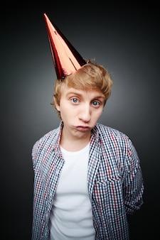 Sad boy with red birthday hat