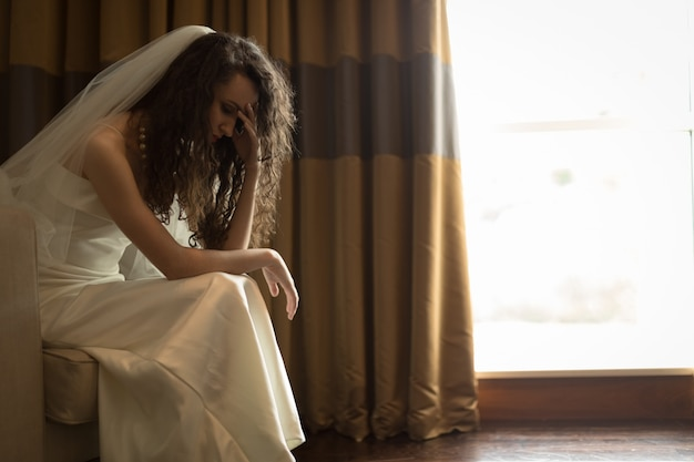 Sad bride sitting with hand on forehead in living room