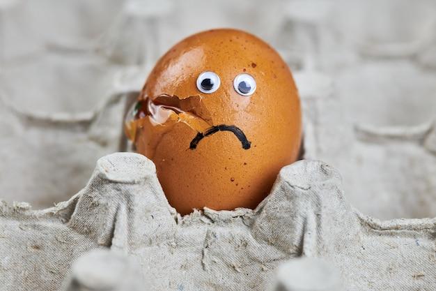 Печальное сломанное яйцо в бумажном лотке для яиц. пасха треснувшее куриное яйцо с глазами, смешные эмоции. концепция повреждения доставки, копия пространства.