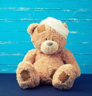 Sad brown bear sits with bandaged white medical bandage head