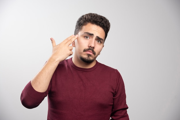 A sad brunette man posing with his hands .