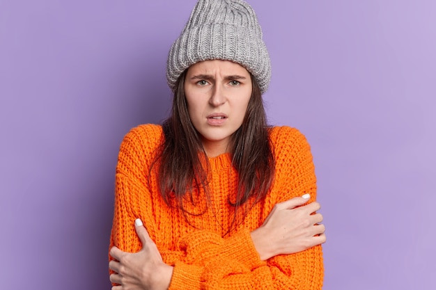 Sad brunette millennial girl with dark hair dressed in knitted wear embraces herself feels cold trembles and looks dissatisfied.