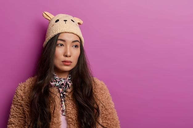 悲しいブルネットの女性はカメラから向きを変え、真面目な思慮深い表情をし、帽子とコートを着て、孤独と不満を感じます