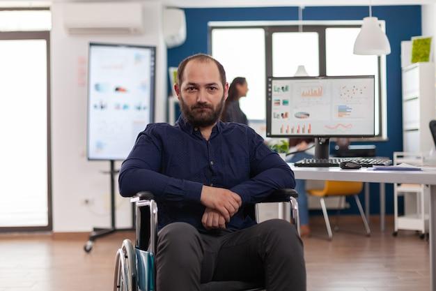 悲しいビジネスマンは、データを使用してpcで作業し、財務情報を処理している営業所の車椅子で麻痺している固定されたカメラを見て、障害に不満を感じていました