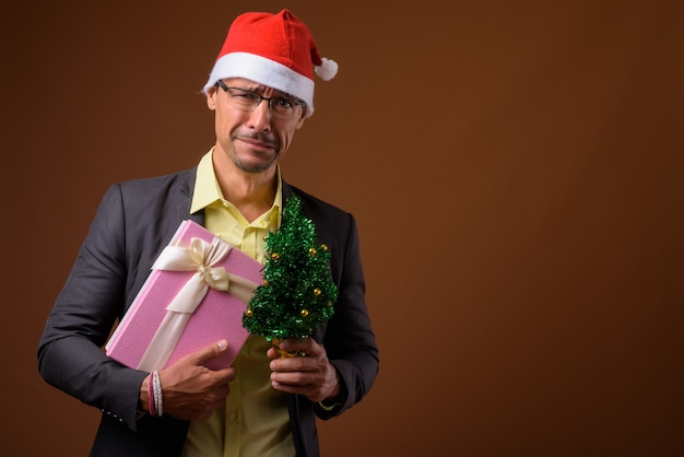 Печальный бизнесмен готов к рождеству на коричневом