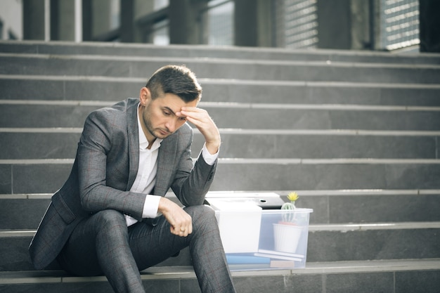 Sad businessman sitting on stairs outdoor with box of stuff as lost business unemployment rate growing due pandemic
