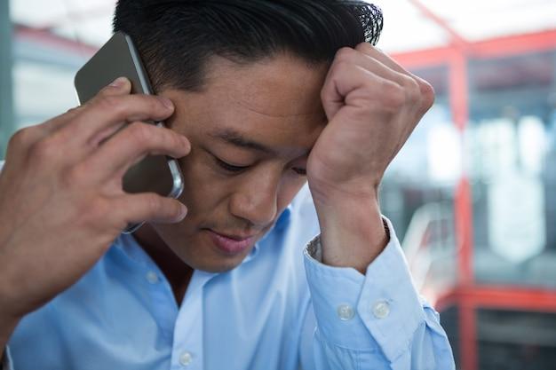 Грустный бизнесмен разговаривает по мобильному телефону