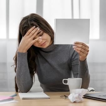 Donna di affari triste che tiene un blocco note in bianco